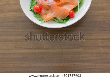 Rocket salad with smoked salmon and cherry tomatoes in a white dish on a wooden table - stock photo