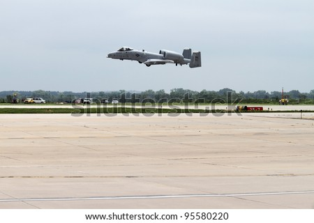 ROCKFORD, IL - JULY 31: A military A-10 Thunderbolt airplane in takeoff motion at the annual Rockford Airfest on July 31, 2010 in Rockford, IL - stock photo
