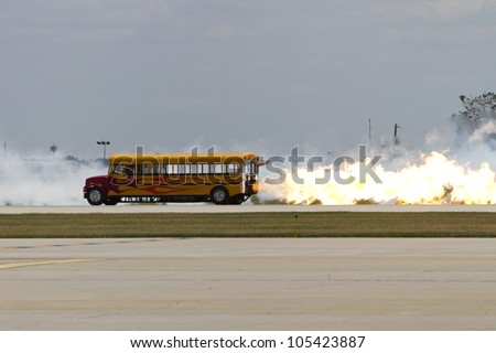 ROCKFORD, IL - JUNE 3: A school bus with a jet engine in a race with an airplane at the annual Rockford Airfest on June 3, 2012 in Rockford, IL - stock photo