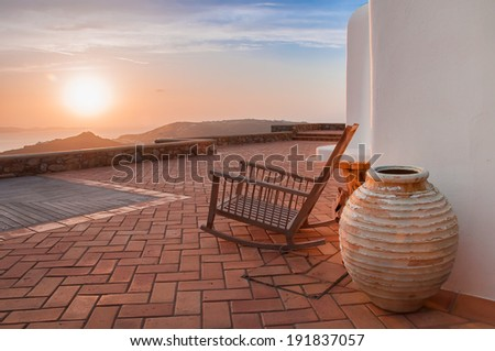 Rocking chair, a clay pot in the yard at sunset. - stock photo