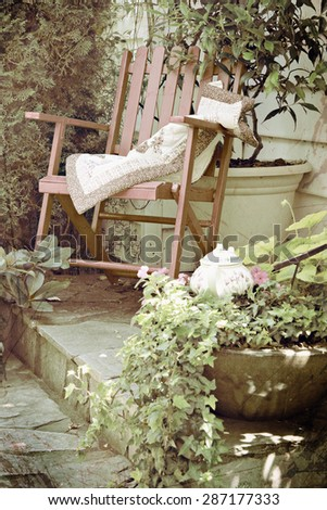 Rocking chair in a cottage garden setting. Double exposure with texture layer and instagram filter.  - stock photo
