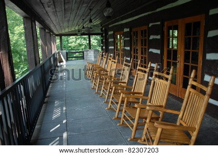 Rocking chairs on the deck of a mountain retreat - stock photo