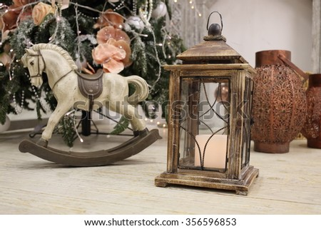 Rocking horse and candlestick are standing near christmas tree. - stock photo