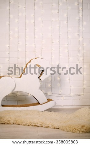 rocking horse in the backdrop of a brick wall with a garland of light bulbs - stock photo