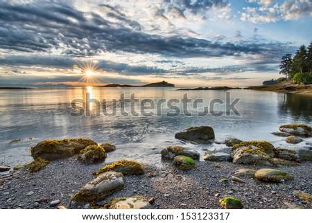 Rocks along coast with sun star - stock photo