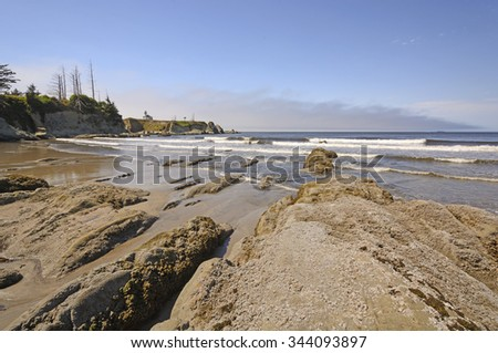 Rocks and Waves on a Sheltered Beach on the Oregon Coast Near Coos Bay - stock photo