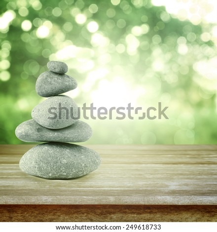 Rocks balancing on table in front of green background - stock photo