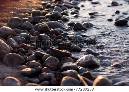 Rocks between the sand beach and the water - stock photo
