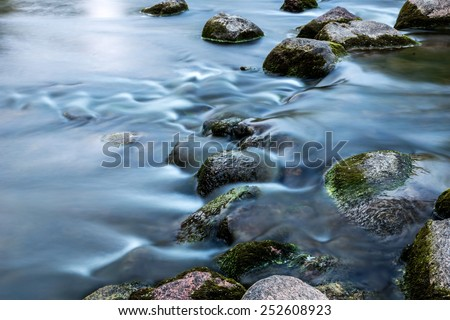 Rocks in stream with smooth flowing water - stock photo