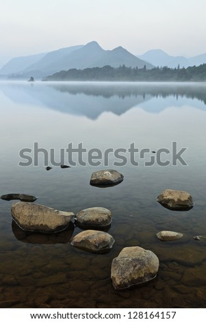 Rocks lying in the still waters of Derwent Water with Catbells reflecting. - stock photo