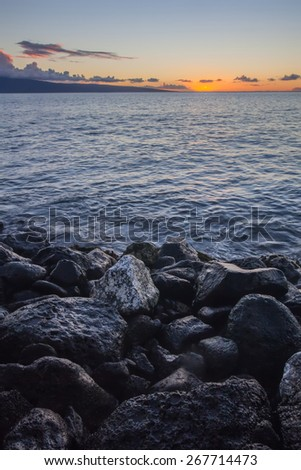 Rocks on beach during sunset in Hawaii - stock photo