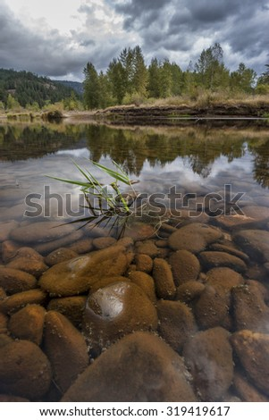 Rocks under the water of the Coeur d'Alene River located in Cataldo, Idaho. - stock photo