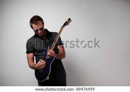 Rockstar playing solo on guitar. - stock photo
