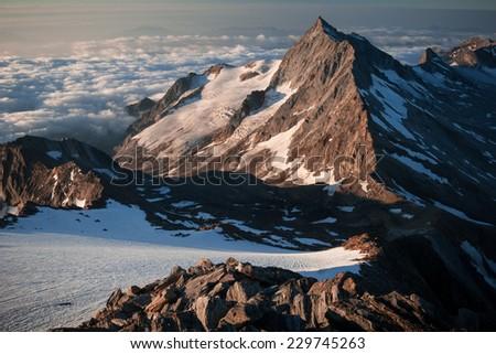 Rocky Alpine mountain summit at sunrise - stock photo