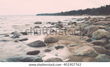Rocky autumn beach with waves crashing on the rocks in misty weather - vintage film effect - stock photo