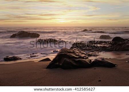 Rocky beach at sunset, north of Portugal. Long exposure. - stock photo