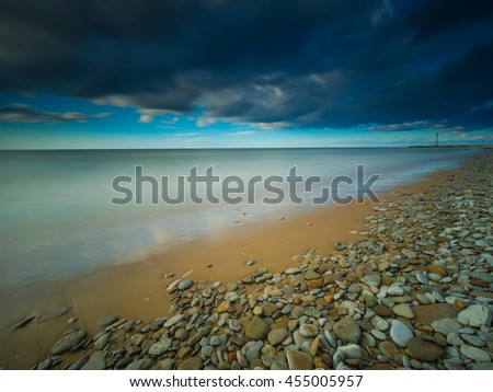 Rocky beach during a beautiful evening. Long exposure photography. Toila, Estonia. - stock photo