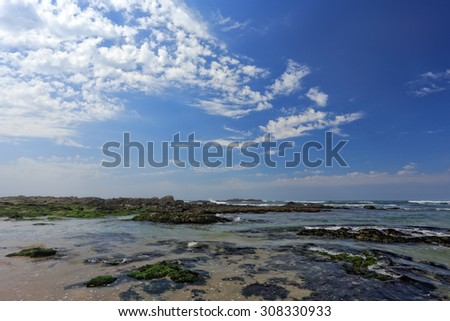 Rocky beach from the north of Portugal during low tide with beautiful blue sky and some white clouds - stock photo
