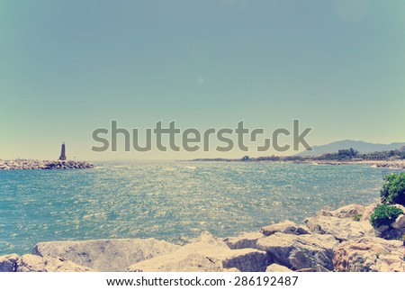 Rocky beach in Spanish luxurious seaside resort Puerto Banus, close to Marbella, on a sunny summer day. Filtered image in faded, washed-out, retro style; summer travel vintage concept. - stock photo