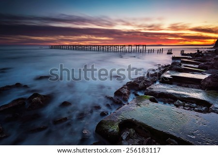 Rocky beach long exposure seascape after sunset - stock photo