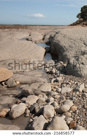 rocky beach scape after reef exposed at low tide  - stock photo