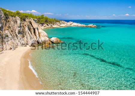 Rocky cliff above the beautiful clear water of the Aegean sea - stock photo