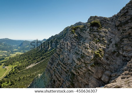 Rocky cliff face near alps showing strata of geologic details under blue sky with copy space - stock photo