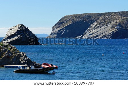 Rocky coast near the village of Cadaques with Cala Nans lighthouse in background, Mediterranean sea, Catalonia, Costa Brava, Spain - stock photo