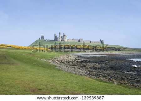 rocky coastline of the northumberland coast of england and the ruins of Dunstanburgh castle - stock photo
