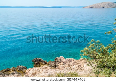 Rocky coastline with bushes and olive trees on the coast of island Krk, Croatia, in the Adriatic sea at the Mediterranean, with other islands at the horizon in the background, on a bright summer day - stock photo