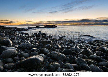 Rocky Coastline with Glow of Sunrise over Ocean - stock photo