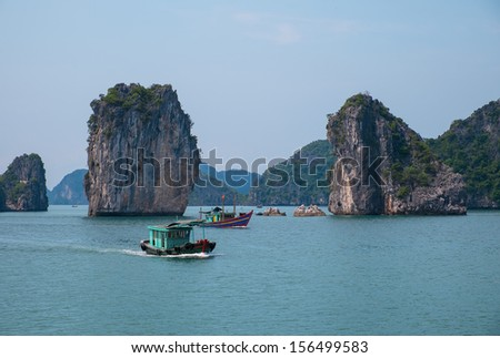 Rocky islands and boats in Halong Bay, Vietnam, Southeast Asia - stock photo