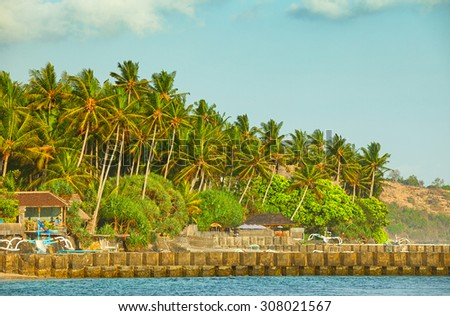 Rocky jetty protects the picturesque coastal town of Candidasa on the island of Bali in Indonesia with coconut palms in the background. - stock photo