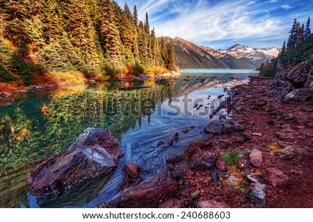 Rocky lakeshore in the mountains with bright foliage - stock photo