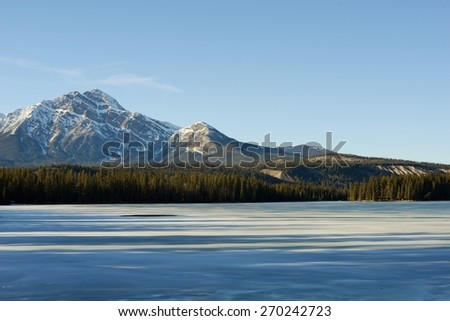Rocky Mountains and Evergreen Forest Behind Beautiful Frozen Lake - stock photo