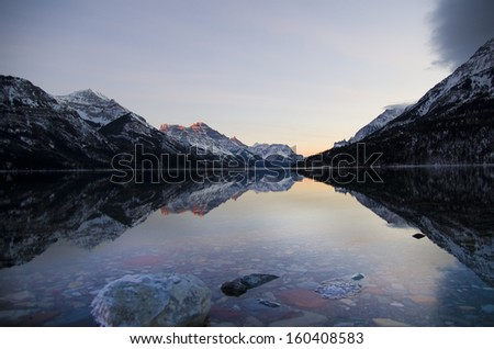 Rocky Mountains in Alberta, Canada and Montana, USA reflected in upper waterton lake. Taken in Waterton Lakes National Park, Alberta, Canada - stock photo