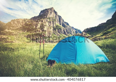 Rocky Mountains Landscape and tent camping with trekking poles and boots Travel Lifestyle concept Summer adventure vacations outdoor - stock photo