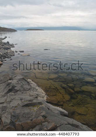 Rocky Northern shore of the lake. Boulders on the beach and in the clear water of the Norilsk lake Keta. - stock photo