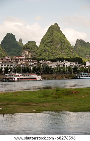 Rocky outcrop mountains in Guilin, China showing the town in the valley and surrounding jungle - stock photo