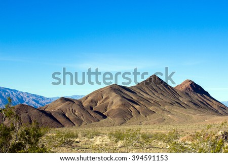 Rocky peaks and desert floor in Death Valley National Park - stock photo