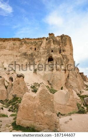 Rocky ridge with dwellings cut into it, Cappadocia, Turkey - stock photo