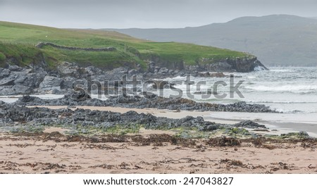 Rocky Scottish coastline with a sand beach in the foreground - stock photo