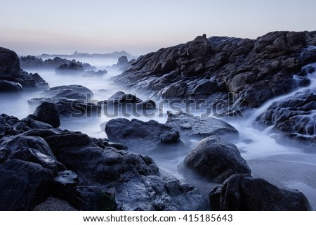 Rocky sea beach at dusk, last sun rays, seeing a salt water cascade during low tide. North of Portugal. Long exposure. - stock photo
