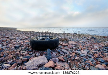 Rocky sea shoreline landscape with an old tyre - stock photo