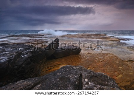 Rocky seascape sunrise scene with distant ocean and colored rocks on the foreground - stock photo