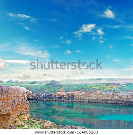 rocky shore in hdr toning under a cloudy sky - stock photo