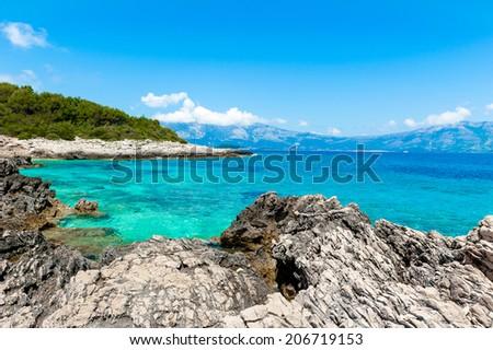 Rocky shore with turquoise sea water. Adriatic coast of Korcula island, touristic destination in Croatia. - stock photo