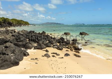 Rocky shoreline looking north towards Waimanalo Bay on Windward Oahu, Hawaii - stock photo