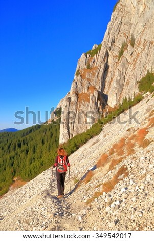 Rocky slope along tall cliffs and hiker woman departing on narrow trail - stock photo