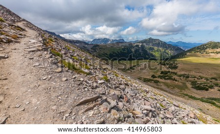 Rocky slopes in the mountains. Amazing view at the peaks which rose against the blue sky. Path on the tops of mountains BURROUGHS MOUNTAIN TRAIL, Sunrise Area, Mount Rainier National Park - stock photo